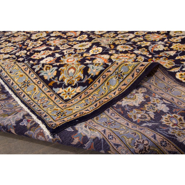 A hand-knotted Kashan rug with an allover floral medallion design on a beige and dark blue field. This amazing vintage rug...