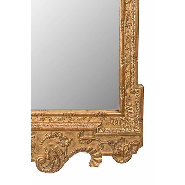 This magnificent English George II style hand-carved and gilt wall mirror has a rectangular mirror plate surrounded by a...