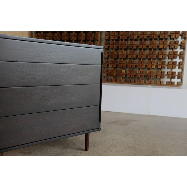 Ebonized four-drawer chest with rosewood legs by Edward Wormley for Dunbar. This piece has been professionally restored.