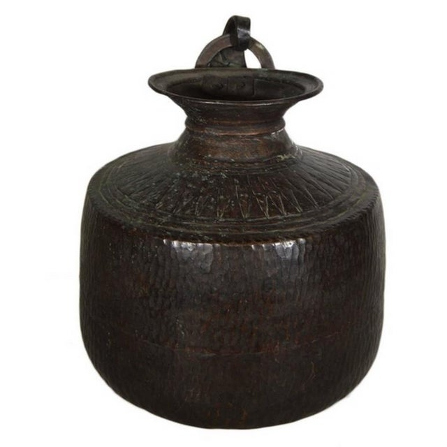 A vintage carved and hand-hammered copper jug from 1930s India. This jug displays a large belly with a round bottom and a...