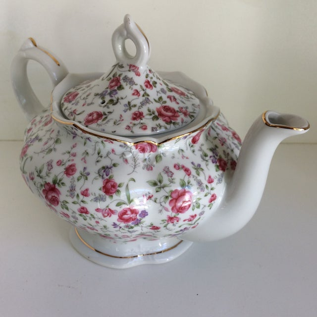 Wonderful Lefton chintz tea pot with working wind up music box hidden underneath. Plays tea for two. Music box is...