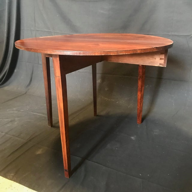 This super early American Hepplewhite inlaid mahogany card table in demilune shape is dated 1810-15. Back leg swings out...