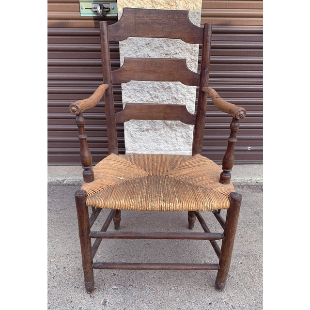 Antique Ash rush armchair from France, c 1820. Features dark ash wood and sloped arms on turned posts. The back slates...