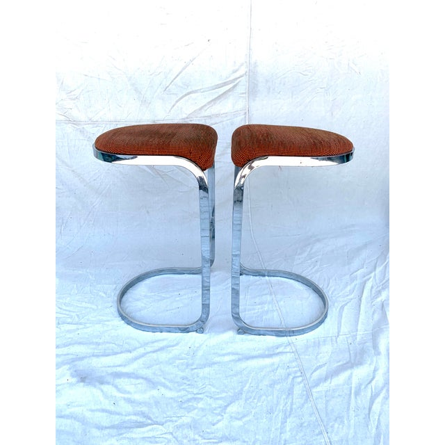 Pair of '70's chrome and upholstery cantilevered bar stools in the style of Milo Baughman. Excellent vintage condition...