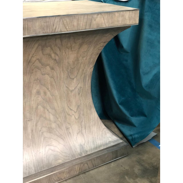 The Montego Console feature rustic quartered white oak veneers and a rustic gray finish. This table has polished stainless...