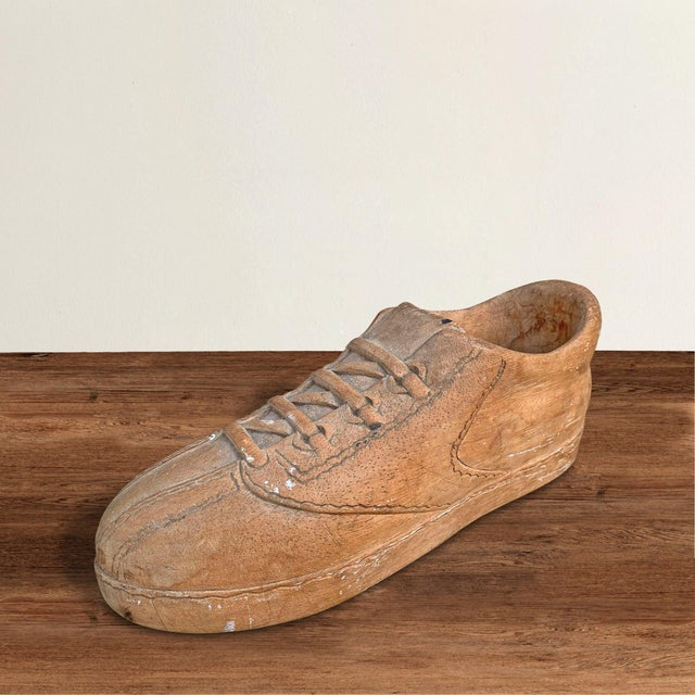 A fabulous mid-20th century American folk art carved wood Adidas shoe with realistic laces, grommets, and rubber sole.