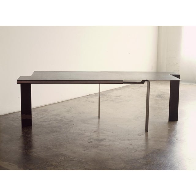 Topographical metal workbench or dining room table folded from a single sheet of cold rolled steel with wax finish.
