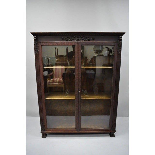 Antique Oak Wood Victorian Glass Two Door Bookcase with Claw Feet, Carved Lions, & Northwind Face. Item features carved...