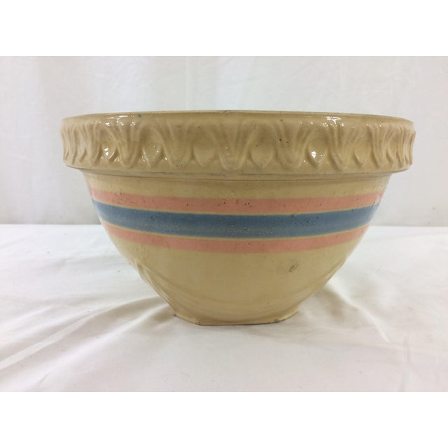 This is a great example of yellowware pottery, with a decorative rim and light blue and coral stripe around. In good...
