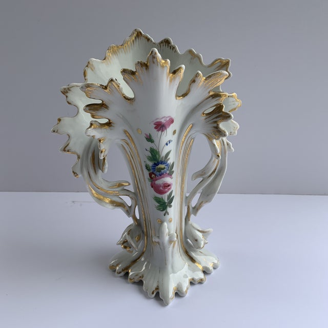 Strikingly sculpted vases with hand painted flowers and gold painted flourishing at every edge.