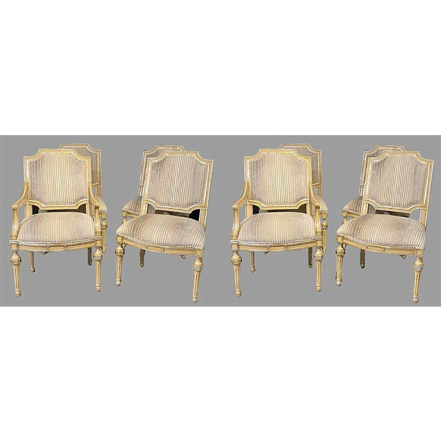 Set of eight Louis XVI style dining chairs. Painted and parcel-gilt decorated. These fine Hollywood Regency Maison Jansen...