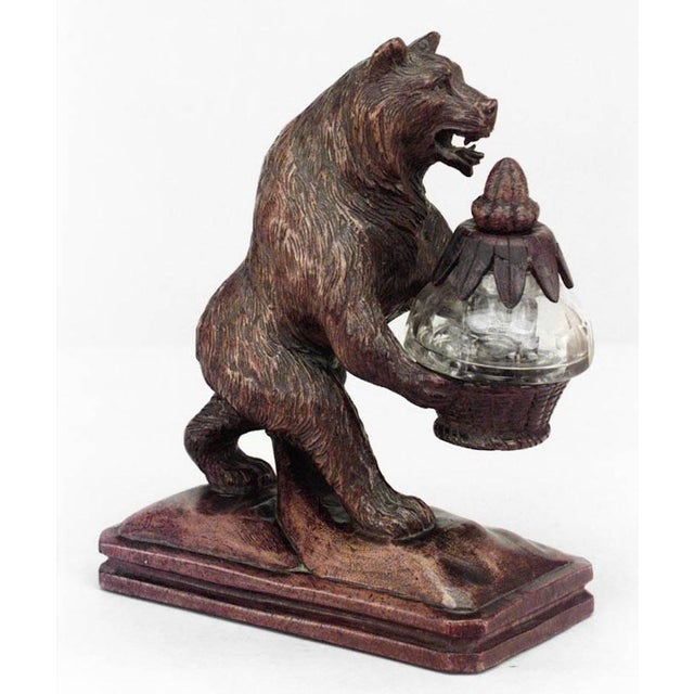 Rustic Black Forest (19th century) walnut figure of bear holding crystal inkwell in carved woven basket with acorn top.