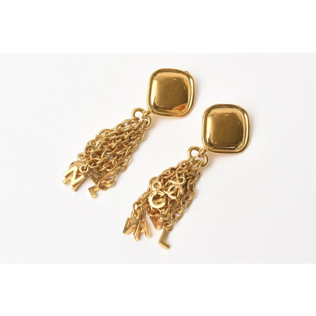 These fun, chic yet sophisticated Chanel clip on dangle earrings have charm like pendants in chain form hanging from the...