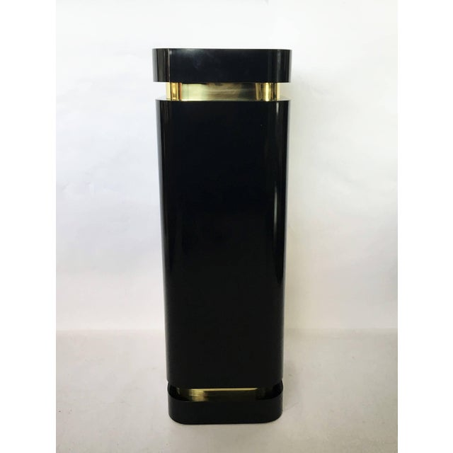 Two unique pedestals in black lacquer with brass trim. The perfect height to display sculptures. Lighted. One is slightly...