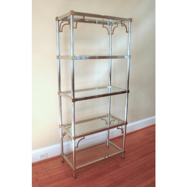 Fabulous midcentury Hollywood Regency chrome and glass shelving unit with brass accents and subtle Chinese Chippendale...