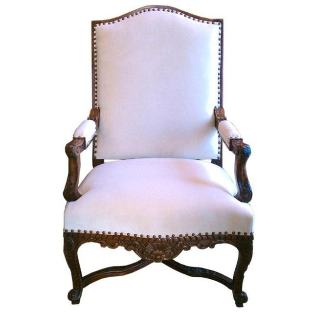 19th century walnut Regence armchair with beautiful hand-carved details. New Upholstery of fine cotton velvet detailed...