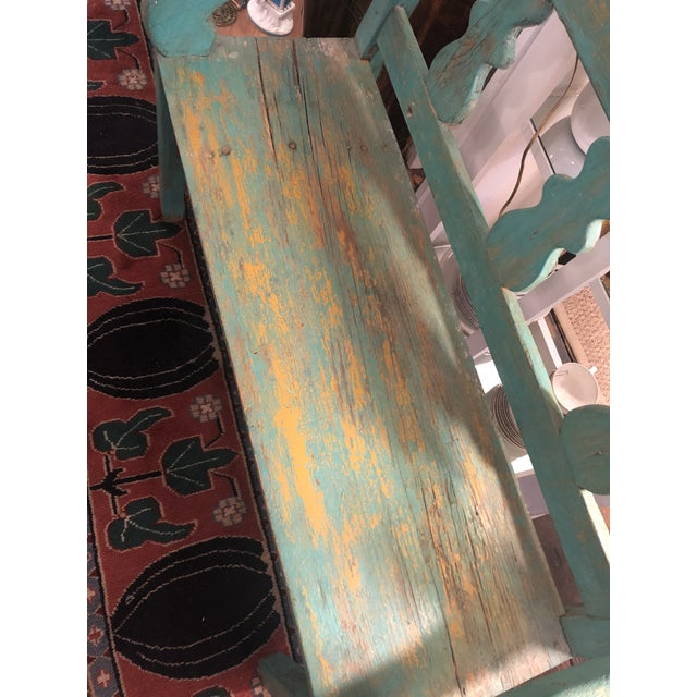 Wonderful old rustic Santa Fe bench having original weathered turquoise paint with yellow undercoat showing through. arm...