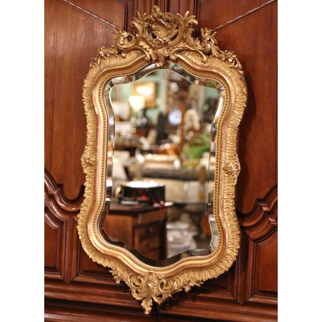 This elegant antique mirror was crafted in France, circa 1880. The pediment features an ornate floral motif cartouche in...