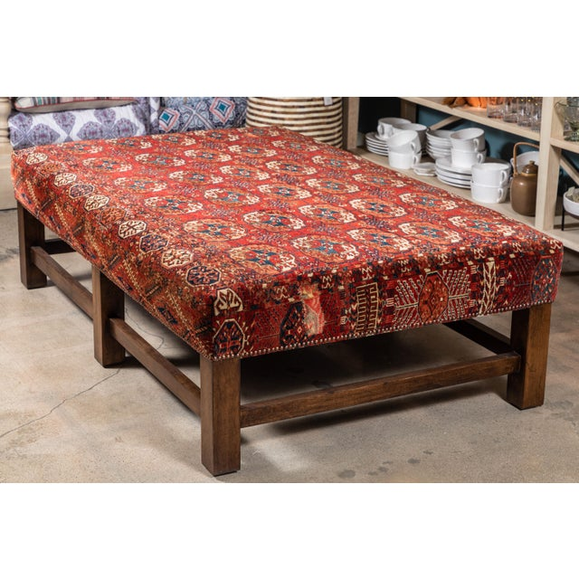 This large scale upholstered ottoman table was custom made to feature a colorful and rich vintage rug with two artfully...