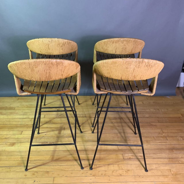 The classic bar stool by Arthur Umanoff has paper cord (jute or rush) contoured seat backs that continue down the side and...