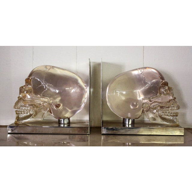 An unusual pair of skull bookends mounted on silver plated stands. The molded skulls are in clear lucite with acrylic jaws...