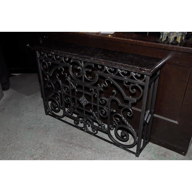 Cast iron console table fitted with a honed granite edged slab atop the antique iron grille.