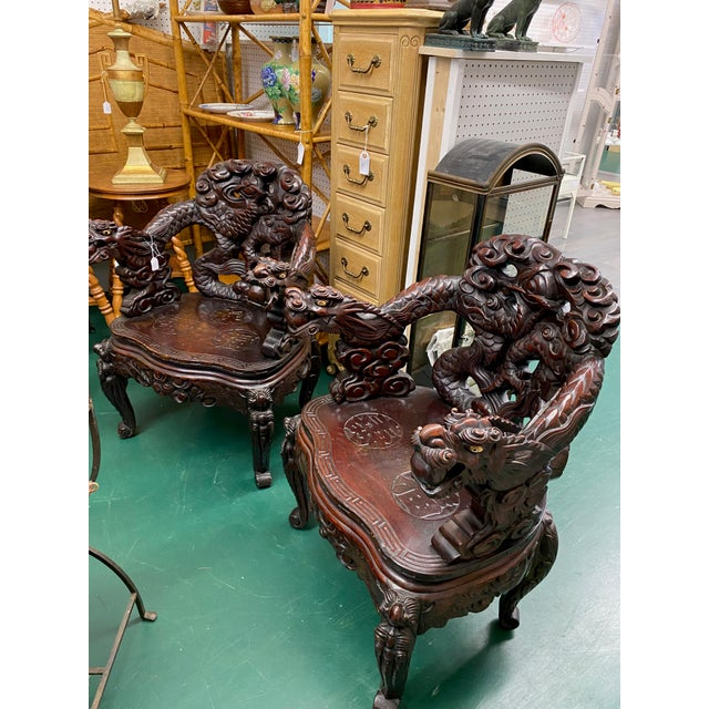 Vintage heavily carved pair of matching Chinese arm chairs made from Rosewood. They are in perfect condition.