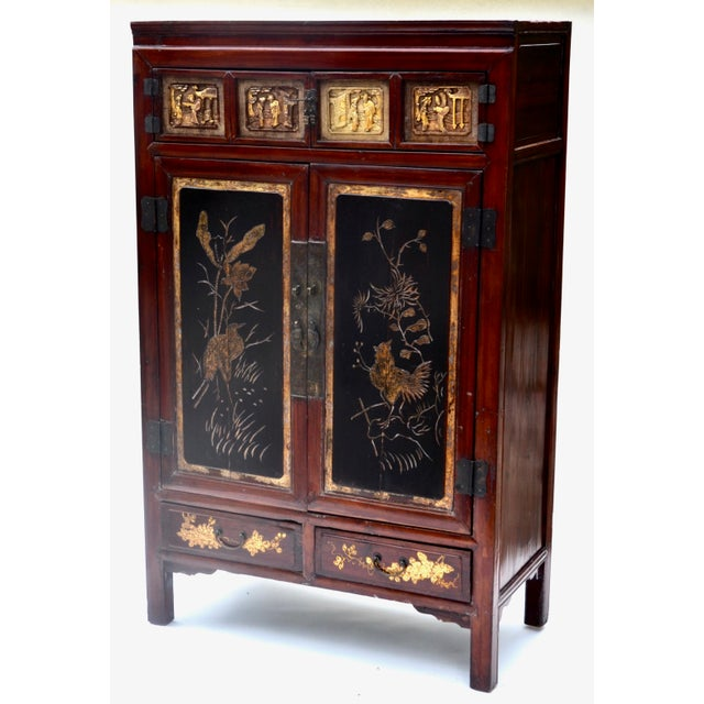 Gorgeous Antique Chinese lacquer cabinet covered in a deep red lacquer, two panel doors with four small panels of carved...