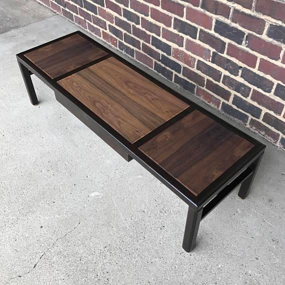 This coffee table by Dunbar features different tones of wood on top of the table. It has a middle drawer that can be...