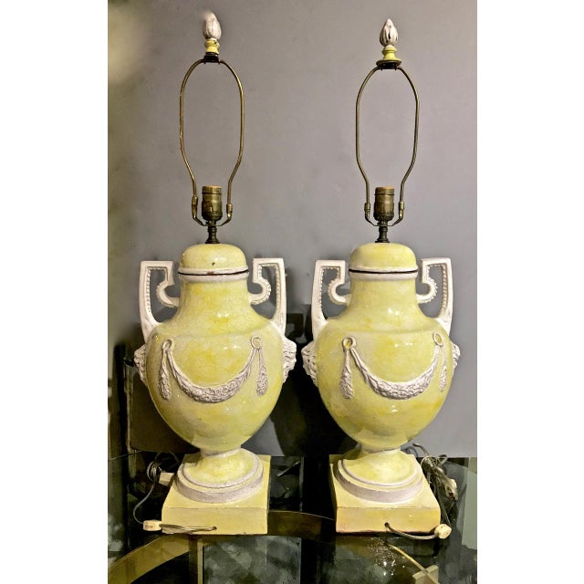 This is an exceptional pair of Mid-Century glazed terra cotta or Majolica lamps with neoclassical urn-form bases. The...