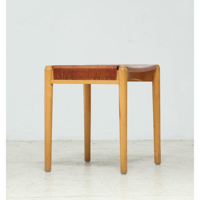 A Swedish stool by Edsby-verken, made of a wooden frame with a bent plywood seating. The plywood has a wonderful and heavy...