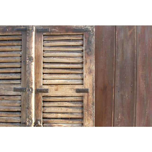 A stunning pair of doors with lots of character. Crafted of teak wood, these doors now wear an aged, oxidized and...