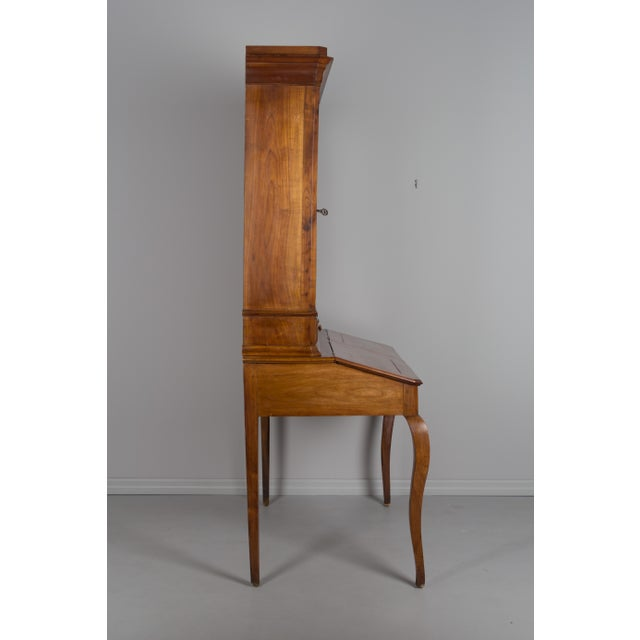 A 19th c. French country slant top desk with bookcase. Made of solid cherry with waxed patina. The top part has original...