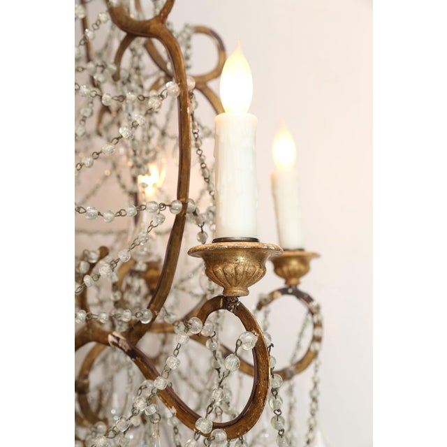 Early 20th century Italian chandelier composed of a turned wood body and scrolled iron arms with hand-blown glass...
