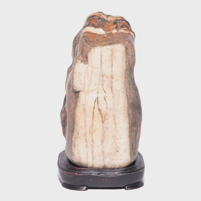 Elevated on a wood base, this mesmerizing dahua stone is displayed like a traditional scholars' rock. Meditating on the...