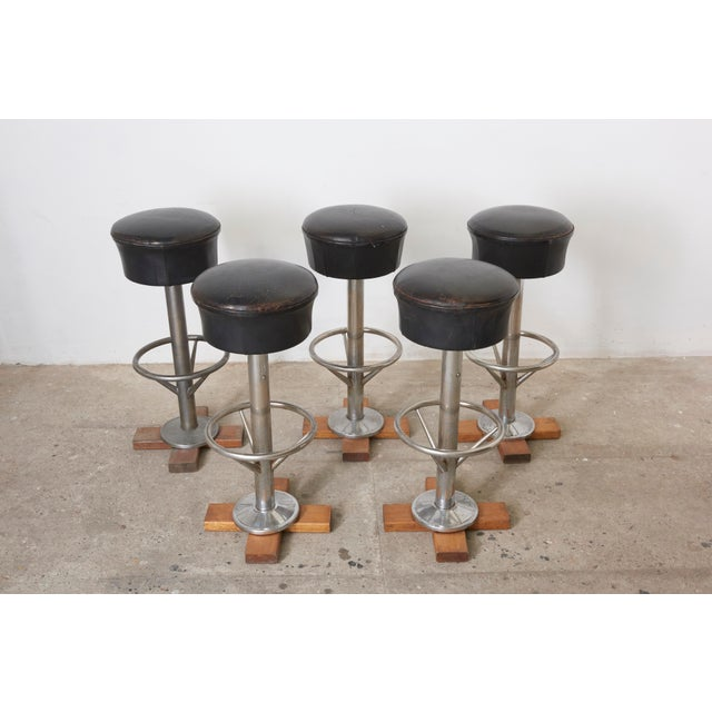 Set of five bar stools with revolving sit in original leather and beautiful patina, the base is chromed steel. These bar...