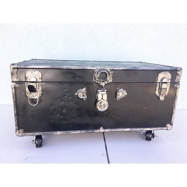 WWII Trunk upcycled by a SoCal artist. Black with a bit of silver and gold tones. It is on heavy duty lockable casters....