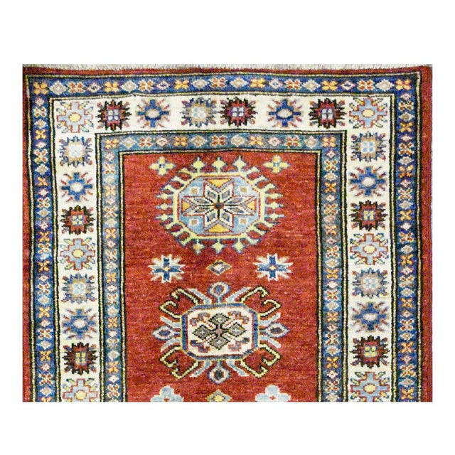 This beautiful Kazak rug is hand made, 100% wool pile, made in Afghanistan. It features a pattern in a vibrant combination...