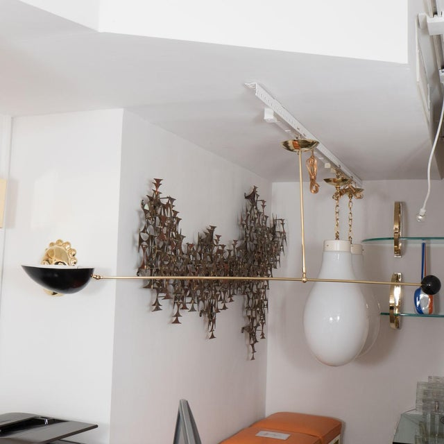Single arm brass and black enameled metal ceiling fixture with articulated shade. Origin: Italy Circa: 1960 Dimensions:...
