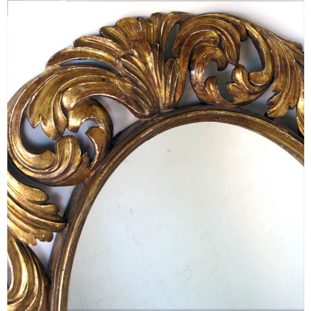 A well-carved Italian baroque style oval gilt-wood mirror; the oval antique plate within a molded slip surrounded by...