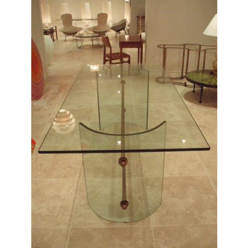 A rare all crystal dining table featuring two inverted c-shaped bases which are held together via two bronze stretcher...