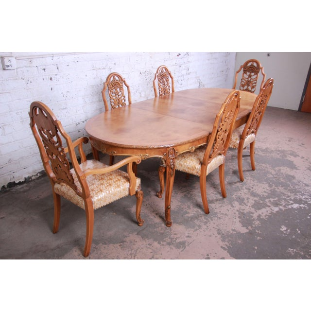Offering a stunning ornate burl wood French carved dining table and six chairs by Romweber. This newly refinished table...
