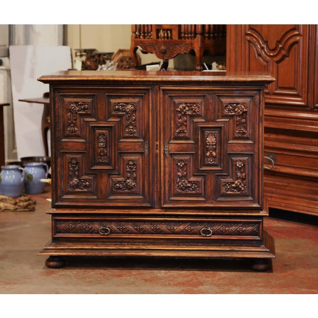 This elegant carved cabinet was crafted in Italy, circa 1860; made of walnut, the tall fruit wood buffet stands on bun...