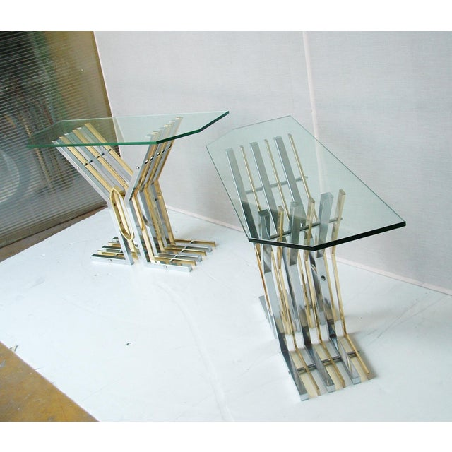 A pair of consoles, chrome and with brass details structure, glass top. made in Italy ca.1970s MEASUREMENTS Height: 74cm...