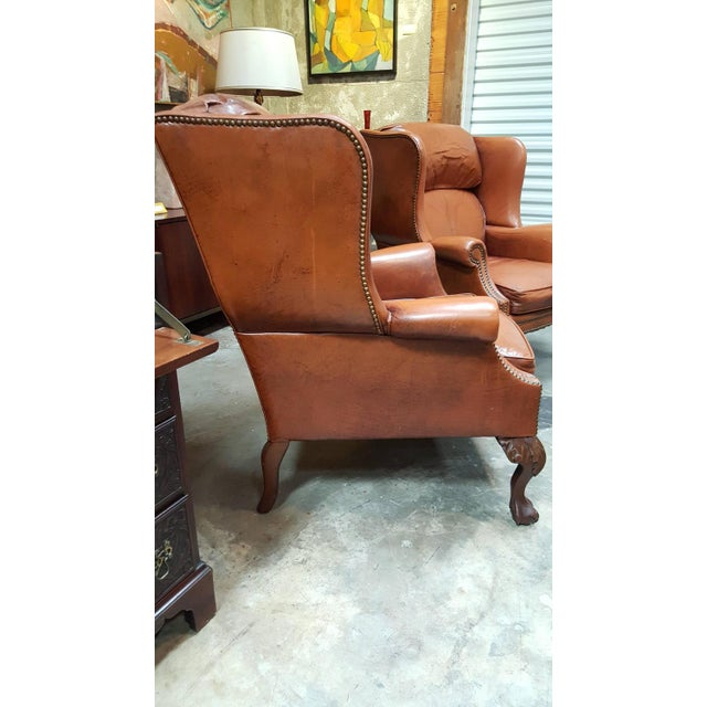 A pair of mid-20th century leather wing chairs by Schafer Brothers Furniture. Classic carved ball and claw leg and brass...