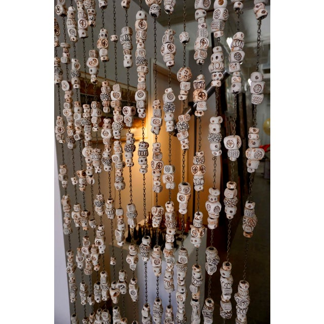 Stamped,etched and carved.Handmade ceramic beads hanging on chain. Can be used as a room divider or wall hanging.