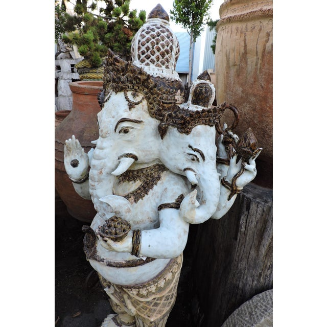 A brown and white-glazed ceramic Ganesh with intricate headdress and multiple heads. The statue has nice details, like the...