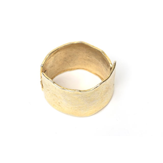 This lovely hinged gold metal vintage cuff bracelet fits well on the wrist. it is hand hammered metal. It has semi...