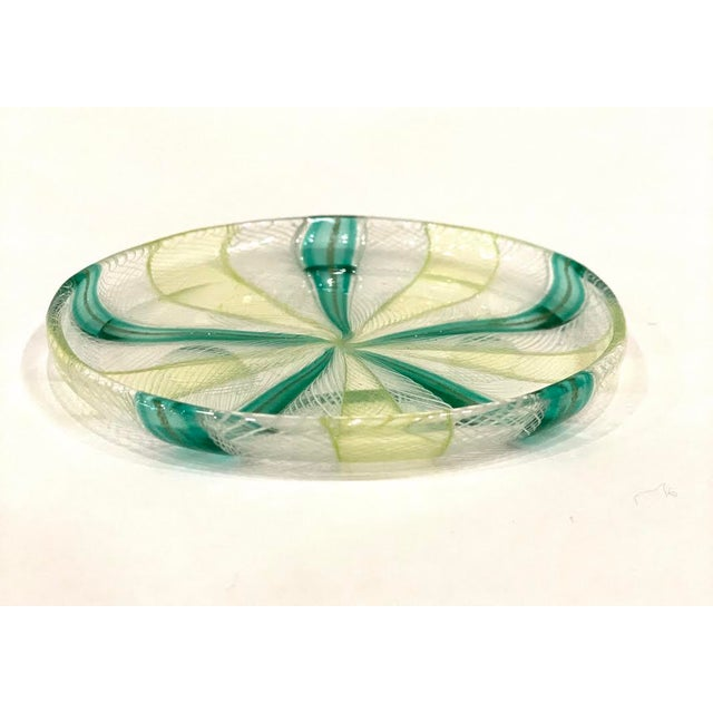 This is a vintage Murano latticino art glass dish. The round dish in shades of emerald green to lime green has a small lip...