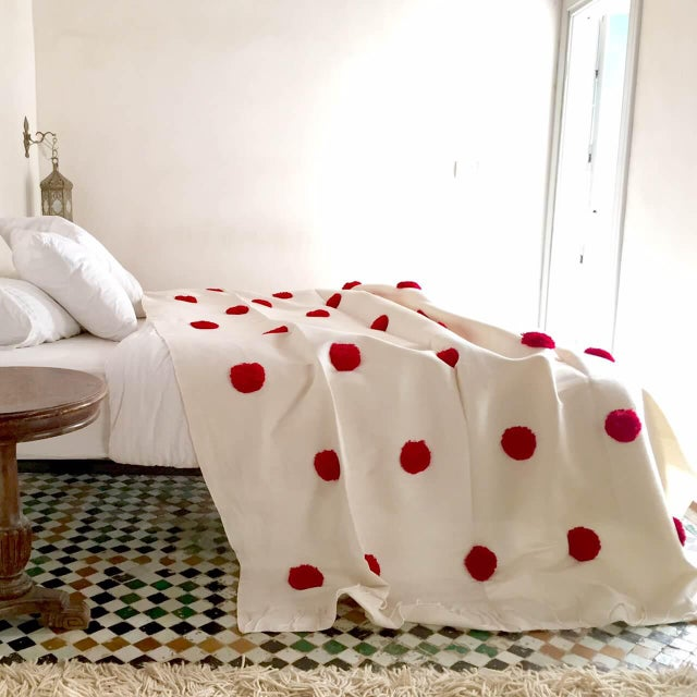 Cotton coverlet with dyed wool pom pom.
